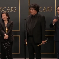 Parasite movie director bong joon ho holding double oscar with his entire team